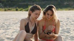 Zwei attraktive Mädchen, die selfie auf dem Strand tun stock video