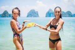 Zwei attraktive Mädchen im Badeanzug auf dem Strand mit Ananas Lizenzfreie Stockfotos