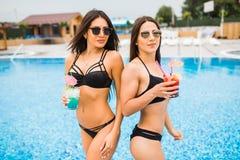 Zwei attraktive Mädchen mit dem langen Haar werfen nahe Pool auf der Sonne auf und trinken Cocktails Sie tragen Badeanzug mit Son Stockbilder