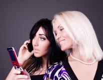 Zwei attraktive Mädchen, die durch Mobile benennen Lizenzfreie Stockfotos