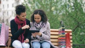 Zwei attraktive Mischrassefrauen mit den Einkaufstaschen, die auf Bank sitzen und Tablet-Computer für das Internet-Surfen verwend stock video footage