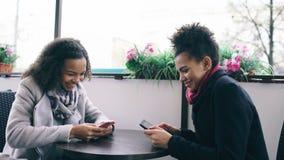 Zwei attraktive Mischrassefreundinnen, die zusammen draußen unter Verwendung des Smartphone im Straßencafé teilen Lizenzfreie Stockfotografie