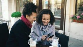 Zwei attraktive Mischrassefreundinnen, die zusammen draußen unter Verwendung des Smartphone im Straßencafé teilen Lizenzfreie Stockfotos