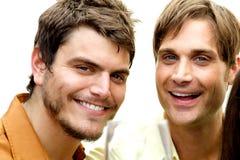 Zwei attraktive Männer, die an der Kamera lächeln Lizenzfreie Stockfotos