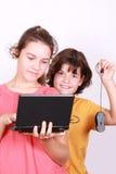 Zwei attraktive Schwestern mit Computer Stockfoto
