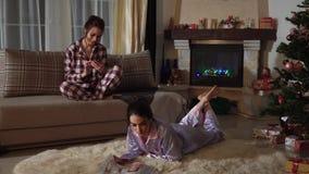 Zwei attraktive Schwesterzwillinge, die in einem gemütlichen Weihnachtsraum in den Pyjamas am Abend Zeitschriften plaudernd und l stock video footage