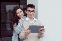 Zwei attraktive Studenten, die im Tabletten-PC dem Campus im Freien lernen und betrachten Lizenzfreie Stockfotos