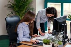 Zwei attraktive weibliche Designer in den blauen Hemden, die zusammen mit neuem Projekt auf PC im modernen Büro arbeiten stockbild