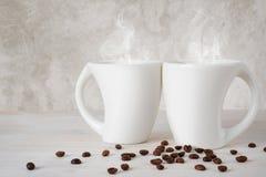 Zwei außerordentliche weiße Kaffeetassen auf Holztisch Lizenzfreie Stockfotos