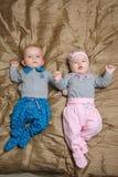 Zwei auf Schlechtem liegende und Gesicht verziehende Babys Stockfotografie