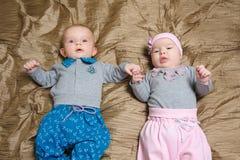 Zwei auf Schlechtem liegende und Gesicht verziehende Babys Lizenzfreie Stockfotografie