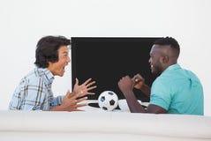Zwei aufgeregte Fußballfans, die fernsehen Stockfoto