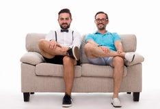 Zwei aufgeregte Männer, die auf Couch sitzen Stockfotos