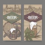 Zwei Aufkleber mit Hand gezeichnetem Bierfaß, Becher, Hopfen, Weizen und Prag- und München-Skizzen auf Papphintergrund lizenzfreie abbildung