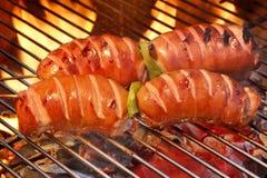 Zwei Aufsteckspindeln mit Wurst auf dem heißen lodernden Grill BBQ stockfoto