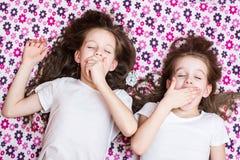 Zwei aufwachende gähnende Mädchen und ein Wecker durchschnittlich stockfotos
