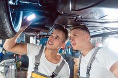 Zwei Automechaniker, welche die Kanten eines angehobenen Autos analysieren Stockfotografie