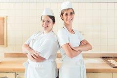 Zwei Bäckerfrauen, die in ihre Bäckerei stolz stehen stockfotos
