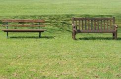 Zwei Bänke auf dem Rasen Stockbild