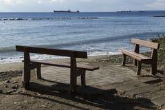 Zwei Bänke auf dem Ufer des Meeres und der Schiffe im Abstand Lizenzfreies Stockbild
