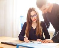 Zwei Büroangestellte, die über Papiere am Schreibtisch sich besprechen Lizenzfreie Stockfotos