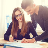 Zwei Büroangestellte, die über Papiere am Schreibtisch sich besprechen Stockbild