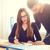 Zwei Büroangestellte, die über Papiere am Schreibtisch sich besprechen Stockfotos