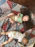 Zwei Babys auf bunter Steppdecke stockbild