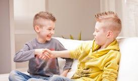 Zwei Babys, die ihre Hände rütteln, da sie Geschäftsmänner waren Stockfotos