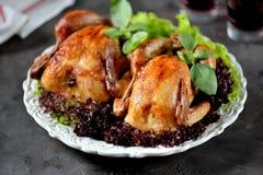Zwei backten Huhn mit Kopfsalat auf weißer Platte und schwarzem Hintergrund lizenzfreies stockbild