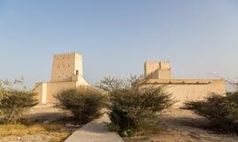 Zwei Barzan-Wachtürme hinter Wüstenbüschen, Katar lizenzfreie stockbilder