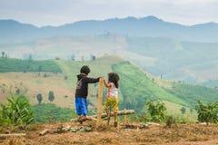 Zwei Bauernmädchen sind das Spielen im Freien mit Bergen im Hintergrund lizenzfreie stockfotografie