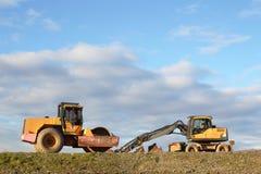 Zwei Baumaschinen auf ungebildetem Gelände stockfotos