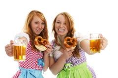 Zwei bayerische Mädchen mit Brezeln zujubelnd mit Biene Lizenzfreie Stockfotografie