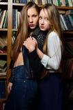 Zwei beautiul Frauen, die in der Bibliothek halten lizenzfreie stockfotos