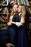 Zwei beautiul Frauen, die in der Bibliothek halten stockbilder