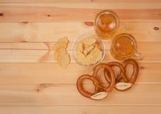 Zwei Becher Bier, Kartoffelchips und gesalzene Brezeln auf rustikalem Holztisch lizenzfreies stockbild