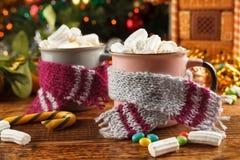 Zwei Becher in den Schals mit einem heißen Getränk und in den Eibischen auf dem Hintergrund eines Lebkuchenhauses und des Weihnac lizenzfreie stockfotografie
