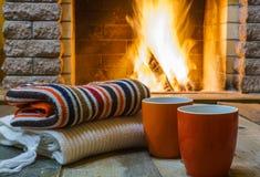 Zwei Becher für Tee oder Kaffee, woolen Sachen nähern sich gemütlichem Kamin stockfotografie