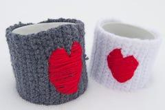 Zwei Becher mit roten Herzen auf Schnee Stockfotografie