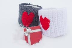 Zwei Becher mit roten Herzen und Geschenk auf Schnee Lizenzfreie Stockfotografie