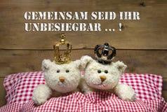Zwei beige Teddybären in der Liebe, die im Bett mit Kronen liegt. Lizenzfreies Stockfoto