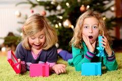 Zwei überraschte Mädchen mit Weihnachtsgeschenken Lizenzfreie Stockfotografie