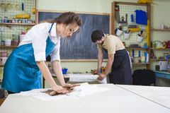 Zwei Berufsarbeitskräfte, die Clay Pieces auf Tabellen in der Werkstatt vorbereiten Stockfotos