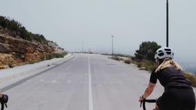 Zwei Berufsstraßenradfahrer reiten ihre Fahrräder auf einen Hügel stock footage