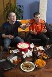 Zwei besorgt beim Sportspiel im Fernsehen aufpassen, vertikal Lizenzfreie Stockfotografie