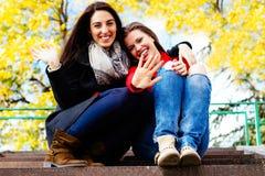 Zwei beste lächelnde und wellenartig bewegende Freunde Stockfotografie
