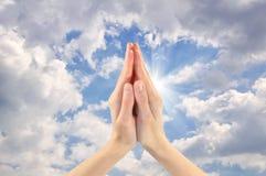 Zwei betende Hände, die den Himmel gegenüberstellen Stockfotos