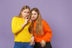 Zwei bezaubernde junge blonde Zwillingsschwestermädchen in der klaren bunten Kleidungsstellung, Kamera auf Pastell schauend stockbilder