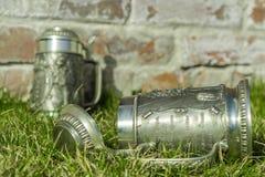 Zwei Bierkrüge auf dem Gras nahe der Backsteinmauer Lizenzfreies Stockfoto